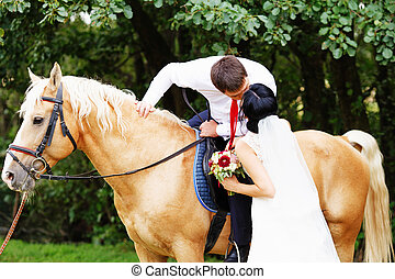 bride and groom on a horses in the forest
