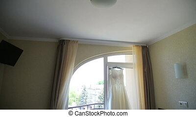 Wedding bride's dress hanging on a window