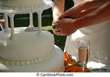 Wedding Cake - A bride and groom cut the cake at their...