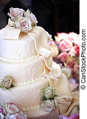 Wedding cake with thick creamy frosting and dried roses as decorations. This image has a shallow depth of field
