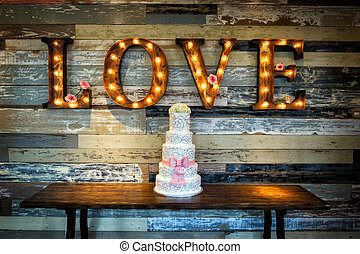 Image of a wedding cake with the word love as sinage on a rustic background