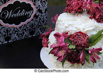 Wedding cake with purple flowers - Layered wedding cake with...