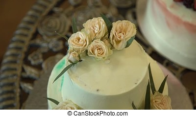 Wedding cake with roses. Beautiful big wedding cake with three storey decorated by tender sweet roses. Outdoor. a white wedding cake with three levels and red roses