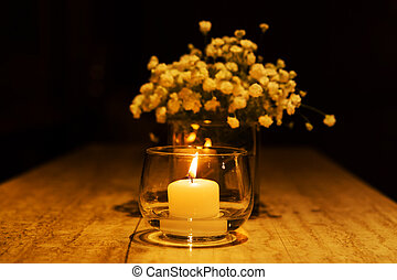 Wedding candle on a table with flowers.