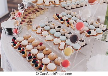 Wedding candy bar. Delicious creamy desserts with fruits, macarons, cakes and cookies on table at wedding reception in restaurant. Luxury catering service.