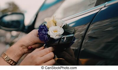 Wedding car decorated with beautiful wedding flowers on the door handles