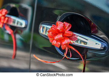 Wedding car of door decorated with red ribbon flower