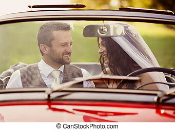 Wedding car with bride and groom