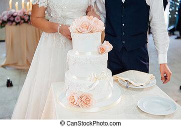 Wedding ceremony. Bride and groom cutting cake
