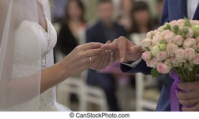 Wedding ceremony: bride puts a ring on groom hand