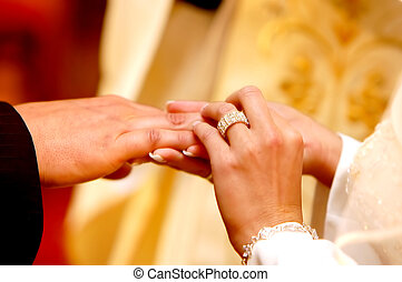 Wedding ceremony, Groom put a ring on bride hand.
