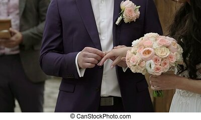 Wedding ceremony: groom puts a ring on bride hand