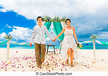 Wedding ceremony on a tropical beach in blue. Happy groom and bride under the arch decorated with flowers on the sandy beach. Rose petals fall from above. Wedding and honeymoon concept.