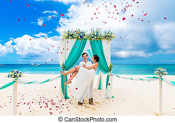 Wedding ceremony on a tropical beach in blue. Happy groom...