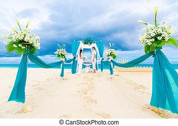 Wedding ceremony on a tropical beach in blue. Happy groom...