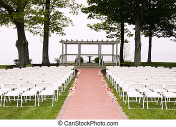 white chairs arranged for a wedding by the lake