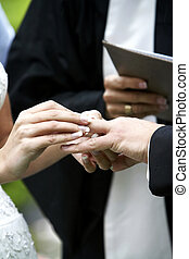 Wedding ceremony ring exchange - Putting the ring on the ...