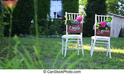 Wedding chairs on the grass. Groom bride.