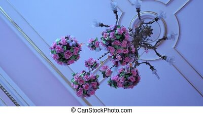 Wedding chandelier decorated with flowers.