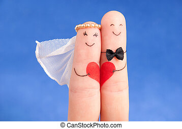 wedding concept - newlyweds painted at fingers against blue...