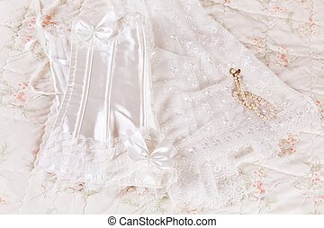 White lace wedding corset and bridal veil on a bed