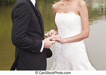 wedding couple are swearing lifetime loyality in the park in...
