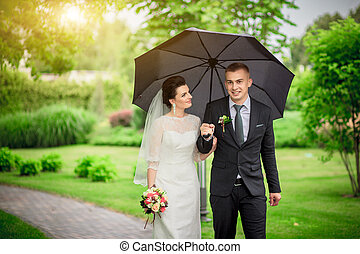 wedding couple, beautiful young bride groom standing in a park holding hands and smiling