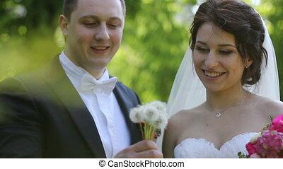 wedding couple blowing on a dandelion