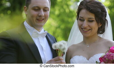 wedding couple blowing on a dandelion