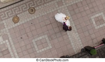 Wedding couple circling in a city street aerial