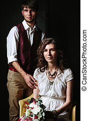 Wedding couple posing in dark interior