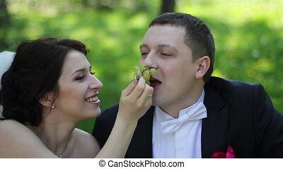 wedding couple eating grape and smiling
