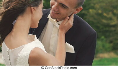 Wedding couple embracing and looking on camera outdoor. Slowly