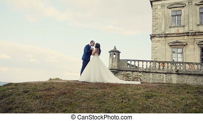 Wedding Couple Embracing Before Castle
