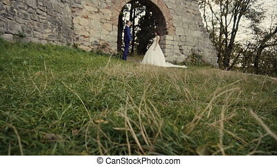 Wedding Couple Embracing Before Old rock Wall