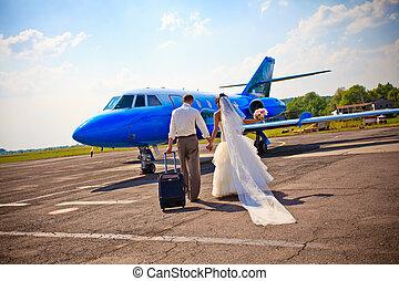 Wedding couple fly on honeymoon - Wedding couple are prepare...