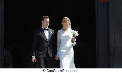 Wedding couple go out of the church after ceremony
