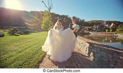 Wedding Couple go to Camera Nature Outdoor Near Lake