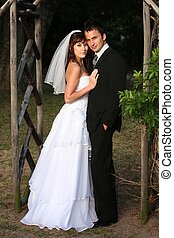 Handsome wedding couple standing under a wooden arch outdoors