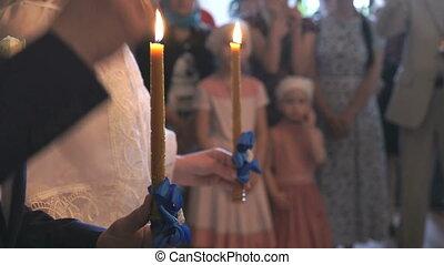 Wedding couple holding burning candles. Close up