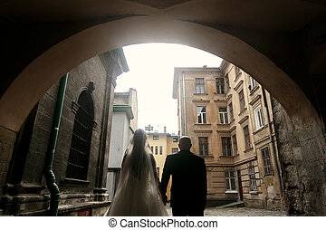 wedding couple holding hand in city street, groom and bride walking in european town in sunshine at old buildings