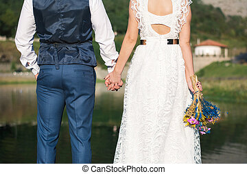Wedding couple holding hands in front of a lake