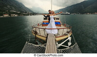 Wedding couple holding hands on the stern of the ship sailing on the sea in Montenegro, Budva