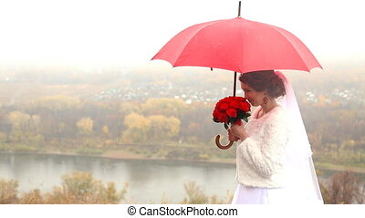 Wedding couple holding red umbrella