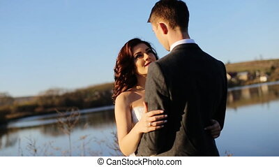 Wedding couple hugging by the lake in the fall shot in slow motion  close up