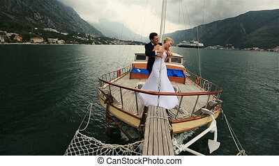 Wedding couple hugging on the stern of the ship sailing on the sea in Montenegro, Budva