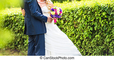 wedding couple hugging, the bride holding a bouquet of flowers in her hand