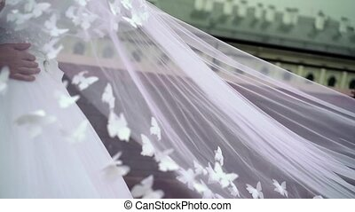 Wedding couple hugging, veil waving at cloudy day