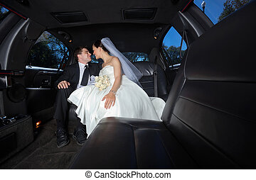 Wedding Couple in Limo - Loving newlywed bride and...
