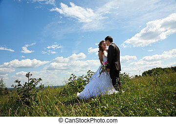 Wedding couple stand in grass in sunny summer day